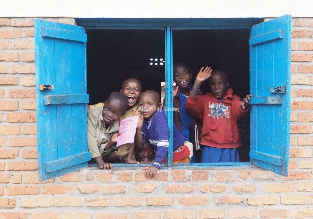 Primary school kids at Groupe Scolaire Kampanga, Northern Province Musanze District, Rwanda, give big smiles and hugs.