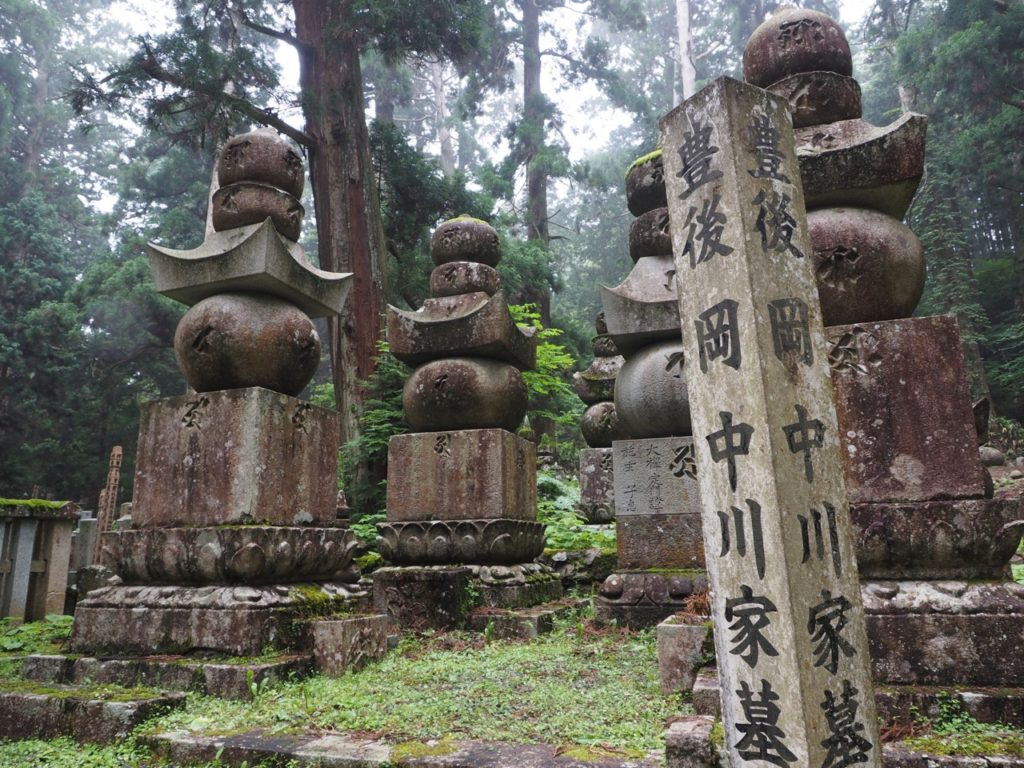 Tombstones and memorials in Okunoin Cemetery in Koyasan (Mount Koya) in Japan. The top 5 objects represent (from the bottom square cube up) – earth, water, fire, wind and space. Image: Alison Binney